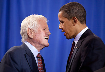 Barack Obama faces Ted Kennedy, both in dark suits in front of a blue backdrop.