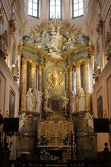 Um altar dourado com seis colunas marvel e várias esculturas em segundo plano