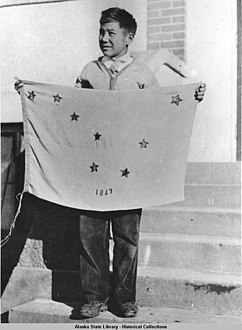 Benny Benson holding the flag of Alaska that he designed.jpg