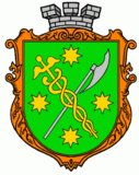 Vert bordure or, a caduceus or and an axe argent saltirewise, four octagrams or in chief, in base and in fess, and overall surmounted by a mural crown argent.