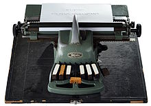 """The machine is T-shaped, has a massive construction and is painted green.  It is mounted on a rectangular board that is apparently part of a transport case.  The part facing the user is narrow and has seven large wooden keys with a white top: six for points 1 to 6 and in the middle between them the space bar protruding forward with its widened end.  The upper, rear part is arranged transversely to it and is reminiscent of the paper carrier trolley of a typewriter.  The paper rollers and the knobs on the right and left are clearly visible.  A sheet of paper is clamped in and shows 2 lines of fully embossed Braille text: """"wikipedia the free encyclopedia"""".  In the middle is a nameplate with the designation """"BLINDENSTUDIENANSTALT - Blista - MARBURG-LAHN-GERMANY"""""""