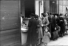 Street scene of people queueing outside a shop