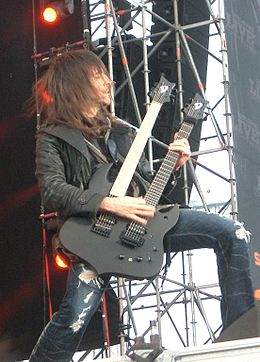 A long brown haired man in a black leather jacket and torn up blue jeans plays a black double necked guitar on a stage.