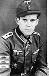 A man wearing a military uniform, side cap, various military decorations including an Iron Cross displayed at the front of his uniform collar.