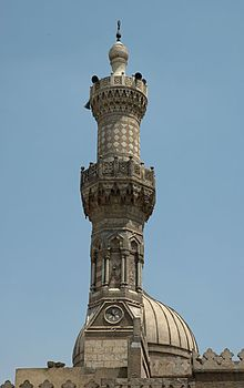 An ornate carved stone minaret, with a carved stone railing around balconies at its center and near its top. The tip of the minaret is a large bulb-shaped stone decoration with a small bulb-shaped metal finial. Behind the minaret part of the top of a dome is visible.