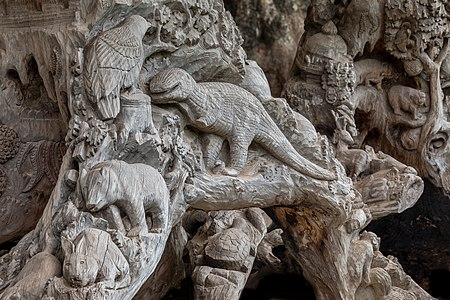 Carved tree with reliefs of dinosaur, bird, bear, rabbit and turtle, as seen in the garden of the Buddhist temple of Haw Phra Kaew in Vientiane, Laos