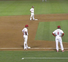 Runners on second and third base, with the third-base coach nearby