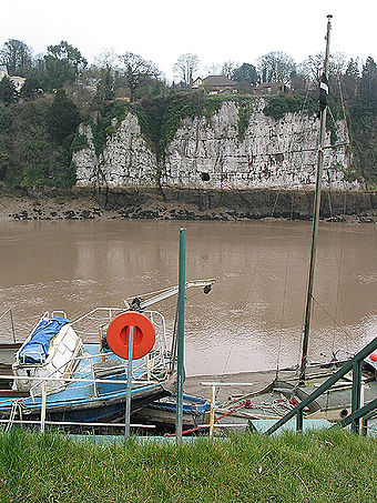 Limestone cliffs seen from the riverside at Chepstow, showing Gloucester Hole, an enlarged natural opening Chepstow Gloucester Hole 1.jpg
