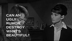 Still shot of a film trailer showing Shirley MacLaine looking down at the left and Audrey Hepburn to her right staring at her, in a bedroom. The words «Can an ugly rumor destroy what's beautiful?» obscure much of MacLaine's face