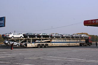 Car carrier trailer - Chinese car transporter. Notice the long length and the double parked upper deck of cars.