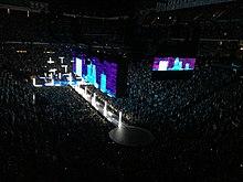 Een donkere fase van bovenaf gezien.  Verticale en horizontale witte palen lichtjes stijgen van zowel het hoofdpodium en uit een lange catwalk in de voorkant van het.  Boven een groot scherm boven de catwalk toont wit-blauw wolkenkrabber beelden tegen een paarsachtig nachthemel