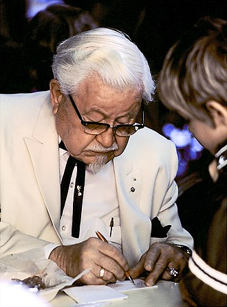 Colonel Sanders - Sanders in costume signing an autograph, 1974.