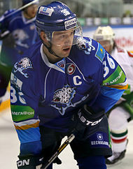 Dmitri Upper in a blue jersey and helmet, holding his hockey stick out