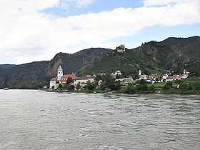 A view of Dürenstein from the river: a small town sits between steep mountains and a wide river. The church tower rises above the several dozen houses. On the mountain above, a ruined castle dominates the sky line.