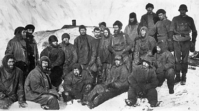 A group of men sitting closely packed together in heavy winter clothes and hats. Snow and ice surrounds them.