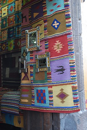Handcrafts and folk art in Guanajuato - Entrance to a handcrafts store in San Miguel de Allende with rug and metal-framed mirrors