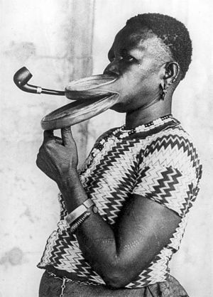 Freak show - Madam Gustika of the Duckbill tribe smoking a pipe with an extended mouthpiece for her lips during a show in a circus. Her lips were stretched by the insertion of disks of incrementally increasing size, similar to some earrings used today. United States, New York, 12 April 1930.