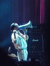 A man dressed in white singing through a megaphone