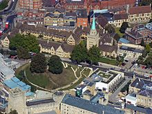 An aerial view of a town; a large grassy mound with two trees to the left; on the far side of the road, two adjoining rectangles of light-coloured stone two-storey buildings with dark tiled roofs, and a tall square stone tower topped with a short metal spire