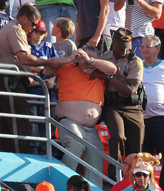 Violence in sports - Unruly spectator cuffed and led away by Miami-Dade Police during NFL match between Miami Dolphins and Buffalo Bills at Sun Life Stadium, December 24, 2012.