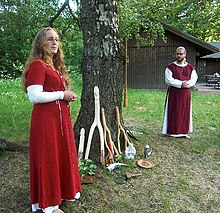 A man and a woman standing outdoors by a tree, wearing red and white robes
