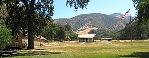 Fort Tejon - Parade ground at Fort Tejon, California, June 2006. The restored barracks are at left and the commanding officer's quarters are at the center, to the right of and behind which are the stabilized but unrestored officers' quarters. Split rail fences outline the foundations of buildings that have not been reconstructed.
