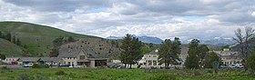 Arka planda tepeler ve ağaçlar olan bir grup bina