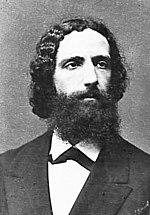 Photographie en noir et blanc, buste d'homme à barbe fournie et cheveux noirs