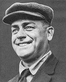 A smiling man wearing a newsie cap