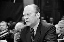 Um homem em um terno está sentado em uma mesa como ele fala em um banco de microfones.  Uma audiência é visível atrás dele.