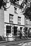 foto van Huis met gepleisterde lijstgevel met ingezwenkte top. Vernieuwde vensters. Hardstenen stoeppalen, verbonden door ijzeren staven