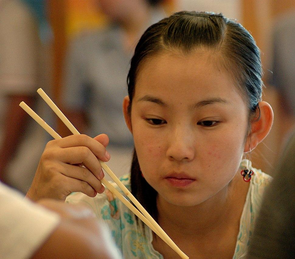 Girl with chopsticks at dumpling restaurant