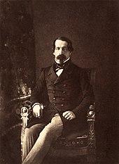 Fotografie alb-negru a lui Napoleon al III-lea care se așează așezat în haine civile, privind în obiectiv.