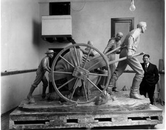 Torleif S. Knaphus - Knaphus in his studio, posing with his 1947 Handcart Monument