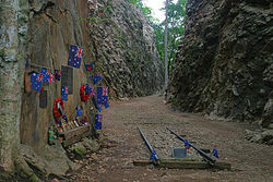 Abandoned railway lines in a deep rocky cutting adorned with memorial flowers