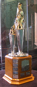 "A silver trophy formed of three cones of differing sizes with spiraling ""ribbons"" at their caps.  It has a wooden base with plates engraved with the names of previous winners"