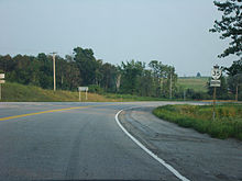 A low perspective of a highway. The highway curves to the right, with rolling hills in the background. A reassurance marker is posted in the ground to the right of the highway