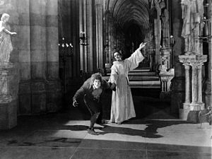 The Hunchback of Notre Dame (1923 film) - Don Claudio restrains Quasimodo from violence.