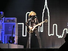 A female blond performer playing an electric guitar on stage. She is wearing black jacket and pants. The backdrops behind her display a number of tall buildings. The stage is illuminated by a number of halogen lights from the ceiling.
