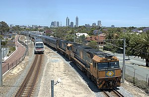 Rail transport in Western Australia -  NR class hauled Indian Pacific departs Perth passing a narrow gauge Transperth suburban train to the left, both trains are on dual gauge track