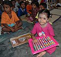 Indian pre-school girl in pink shirt plays with abacus.jpg