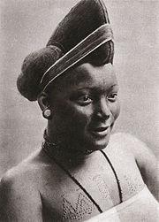 photo noir et blanc d'une femme avec une coiffure tressée en hauteur et portant des scarifications sur le haut de la poitrine