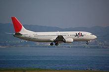 A Boeing 737-400 aircraft painted in new JAL corporate livery with a skyline background