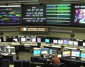 Space Flight Operations Facility - Interior photograph of the control room at the Space Flight Operations Facility, with tables of monitors and workstations arrayed facing several large wall-mounted monitors.
