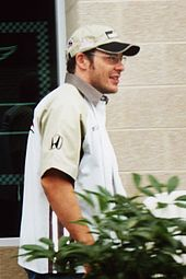 Man in his early thirties wearing a baseball cap and glasses.