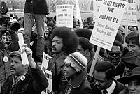 Jackson surrounded by marchers carrying signs advocating support for the Hawkins-Humphrey Bill for full employment, January 1975.