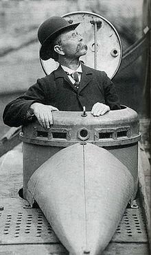 John Philip Holland. Sans E, donc rien avoir un homonyme malheureux. Pionnier des sous marins du début du XXe siècle. Oui, à cette époque un sous marinier peut avoir un chapeau melon.