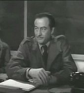 John Emery sitting at a desk