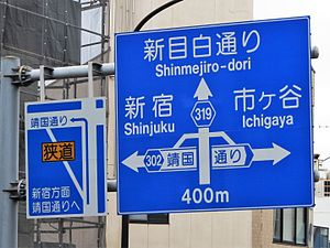 "Rat running - Japanese road sign directing away from a narrow roadway. Left board says ""To Shinjuku, go ahead to Yasukuni-dori Ave."", and the ideograms written in the yellow rectangle mean ""narrow street"""