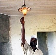 Adam tavandan asılı bir lambayı aydınlatıyor